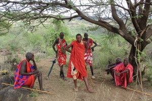 "In rural areas, Maasai men, dress traditionally and periodically meet together to ""eat meat"" and discuss community problems, like predators attacking their cattle."
