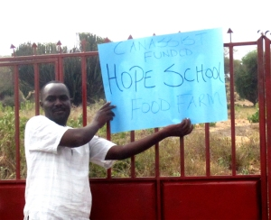 "Kennedy Onyango outside the school gate in early 2012.  Along with CanAssist he was ready to ""plant the seeds"" of development that will help his community."