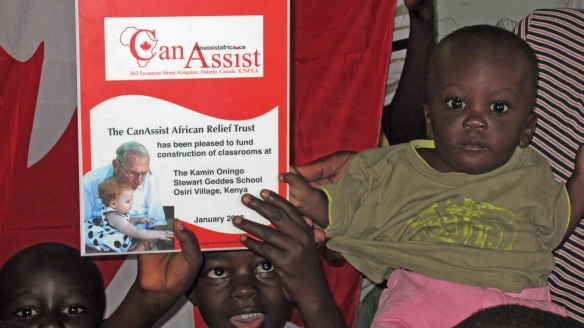 Little Stewart Geddes with a plaque acknowledging the contribution of his namesake to the school in Osiri Village Kenya.