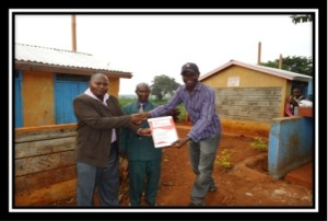 Dan Otieno presents a plaque to Michael Gichira of the Murera group outside the latrines constructed in 2012 with funding from CanAssist.