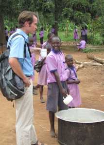Christopher serves up some posho for lunch to visitor, Dave Kay, at Hope for Youth School