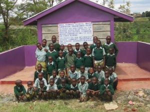 "Inscription on the latrine wall reads "" Twiga Primary School water & Sanitation enhancement project. This project has been funded by CanAssist African Relief Trust in conjunction with the Grey Gates Foundation /Vancouver and the family of Ruth and Donald Redmond."""