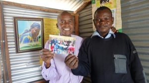 Benta Odihambo's sons, Blasto and Samwel accept the donation from the St Mark's congregation in Barriefield to purchase sanitary pads for the older girls at the school.