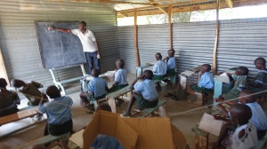 These pupils are being taught in a CanAssist-funded school. Class sizes are manageable, the students have desks. The classroom is rudimentary but clean and the kids receive good teaching.